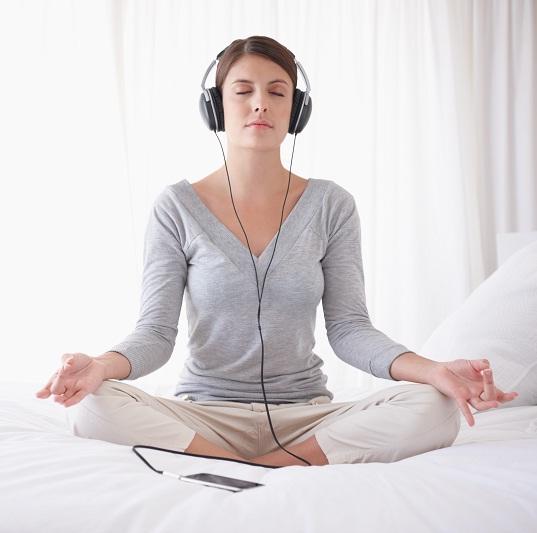 vrouw mediteert met muziek op
